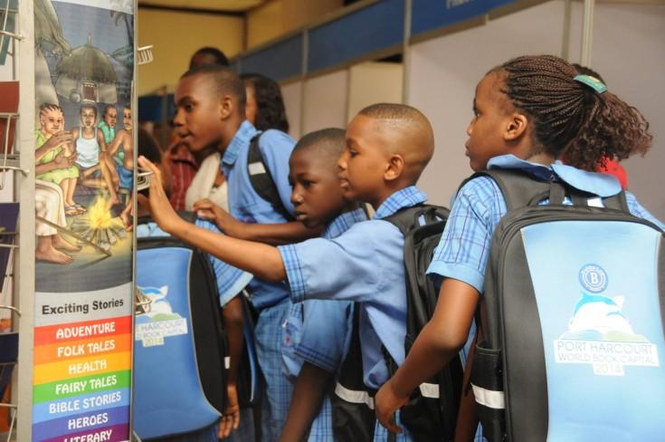 Niños equipados con los materiales del Port Harcourt World Capital Book. / PHWCB