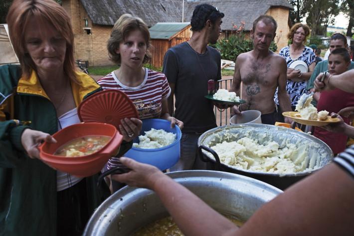 Vecinos de un suburbio de blancos pobres en Sudáfrica hacen cola para recibir comida de la beneficencia, en Krugersdorp, marzo de 2010. Se estima que un total de 450,000 sudafricanos blancos, de entre 4.5 millones de blancos que habitan Sudáfrica, viven debajo del umbral de la pobreza. Foto de REUTERS/Finbarr.