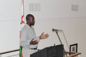 Patrick Kwambi Kabeya, poeta congoleño refugiado en Tongogara, Zimbabwe, recita en la inauguración en Harare. Fotografía de Kwenda Kumbirayi.