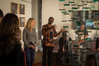 Katrin Peters-Klaphake y Raphael Chikukwa muestran la exposición a la prensa. A la derecha, la instalación de Immy Mali; al fondo, una fotografía de Miriam Syowia Kyambi. Kampala, Uganda.