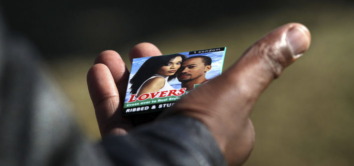 JOHANNESBURG, SOUTH AFRICA - JUNE 16: A Soweto youth holds a free condom he received at a HIV/AIDS awareness event held by the non-profit Population Services International (PSI), ahead of a World Cup game on June 16, 2010 in Soweto, Johannesburg, South Africa. South Africa has the highest number of people living with HIV in the world, where almost one-third of women between the ages of 25-29 are HIV positive. (Photo by John Moore/Getty Images)